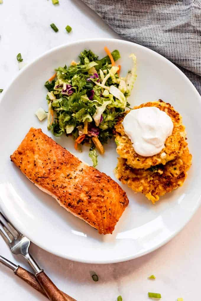 Overhead shot of pan fried salmon with corn fritters and salad