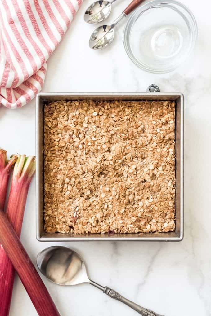 A square baking dish filled with oat crisp topping next to stalks of fresh rhubarb.