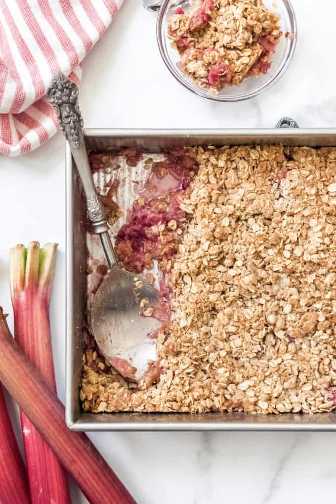 A baking dish with rhubarb crisp and a large serving spoon.