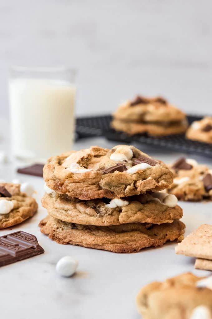 A stack of s'mores cookies in front of a glass of milk.
