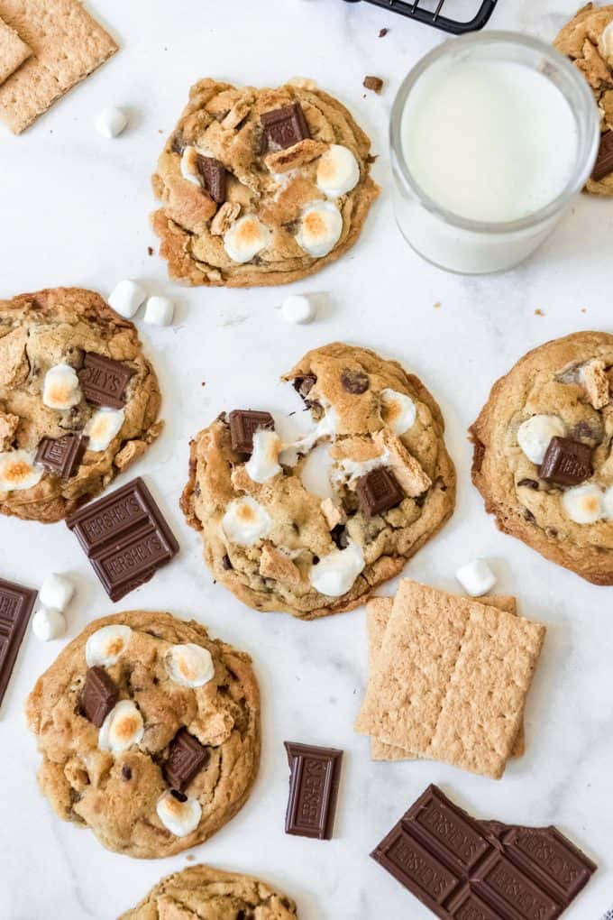 S'mores cookies on a white surface surrounded by graham crackers, marshmallows, and chocolate bars.