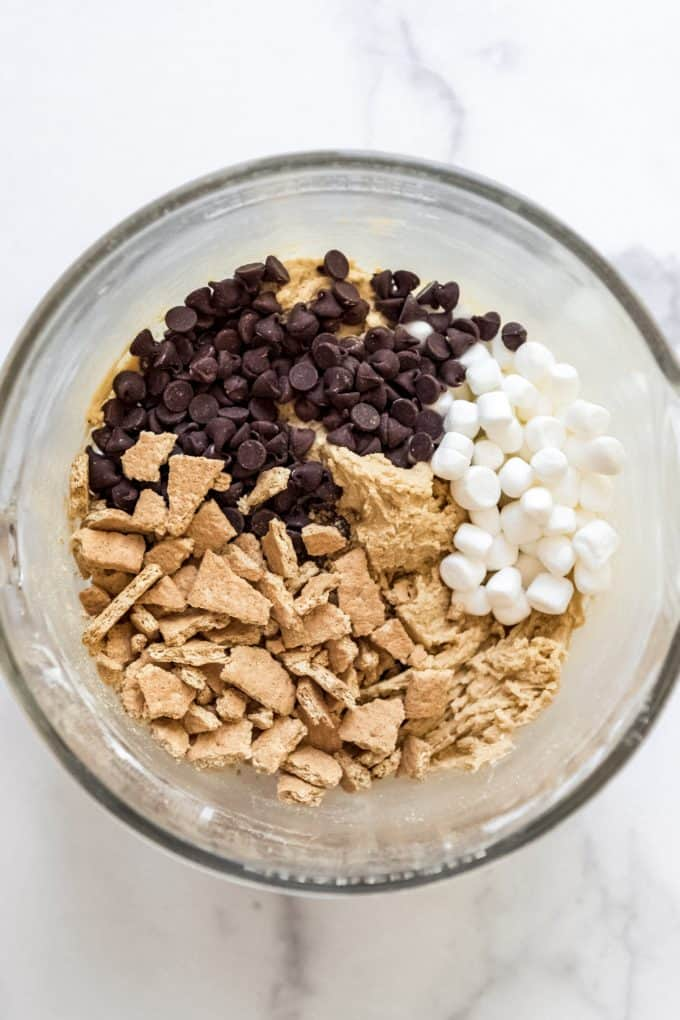 a glass bowl filled with graham crackers, milk chocolate chips and mini marshmallows