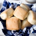 A blue checkered towel in a bowl holding square baked roadhouse copycat rolls inside