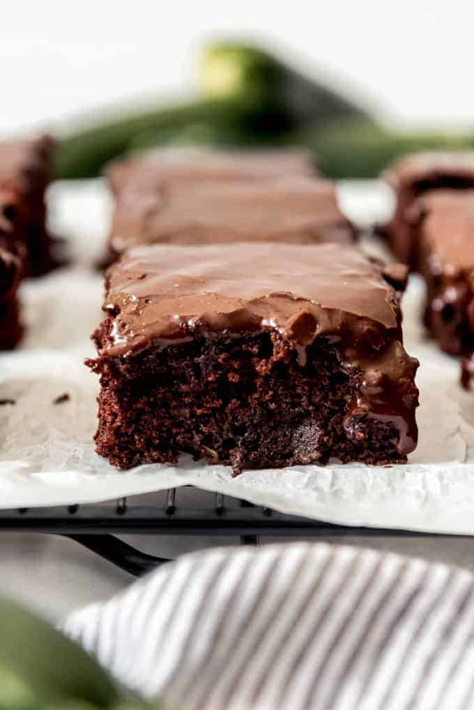 A close image of a moist zucchini brownie with chocolate icing.