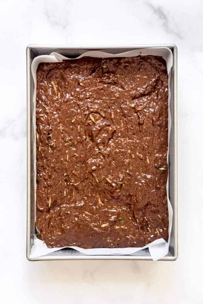a baking dish filled with zucchini brownie batter