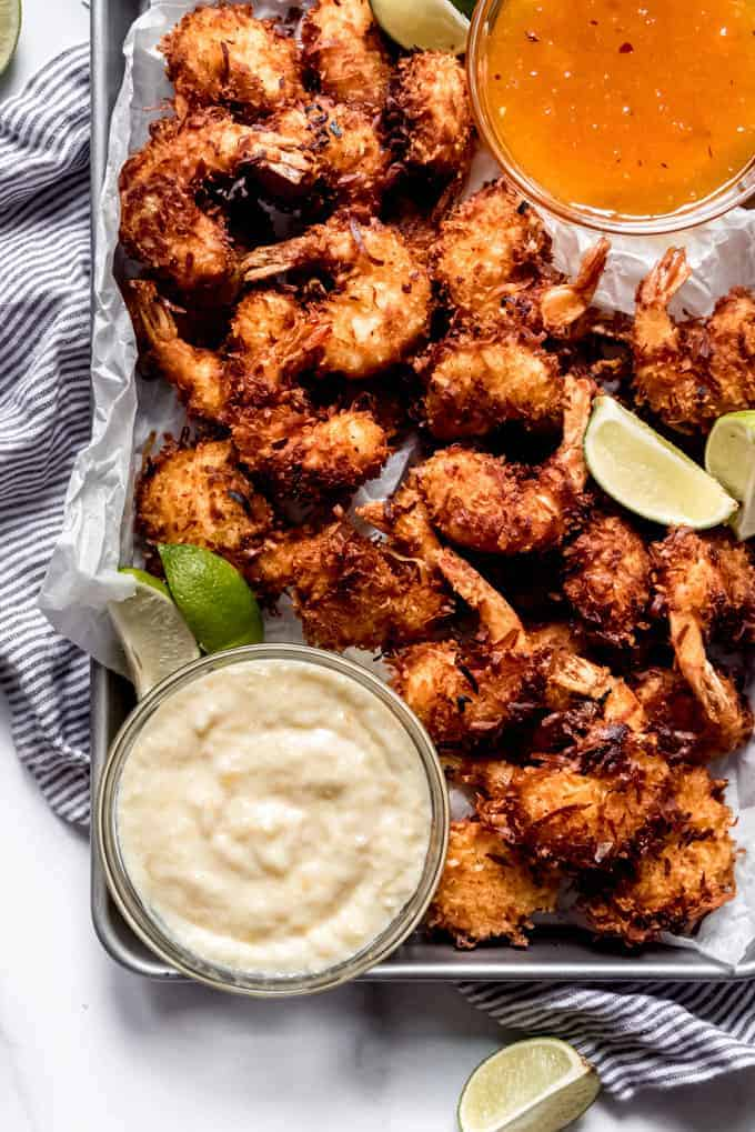Crispy coconut shrimp on a sheet pan with lime wedges and a bowl of dipping sauce.
