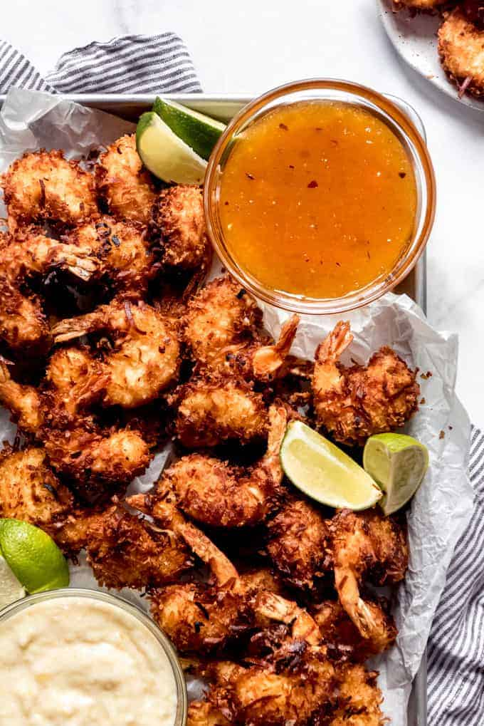 Coconut shrimp on a baking sheet with sweet chili dipping sauce in a bowl next to them.