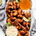 A sheet pan piled with coconut shrimp with lime wedges and two dipping sauces.