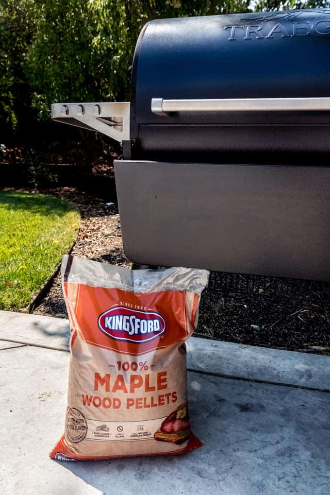 A bag of Kingsford 100% Maple Wood Pellets leaning against a Traeger grill.