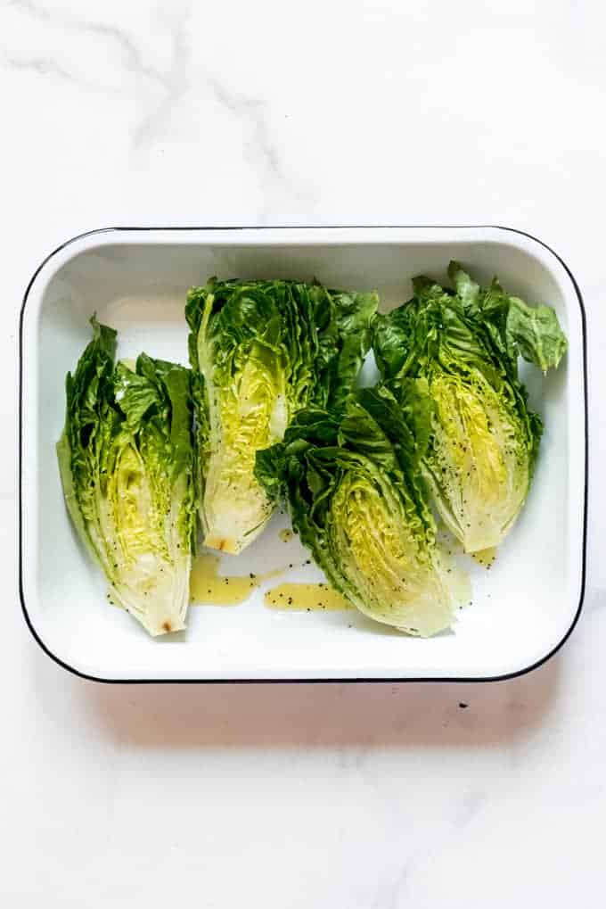 Romaine lettuce that is sliced in half and drizzled with olive oil, salt, and pepper in a white enamel baking dish.
