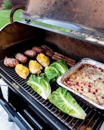A full meal of sweet potatoes, chicken, lettuce, and dump cake being cooked on a Traeger smoker.
