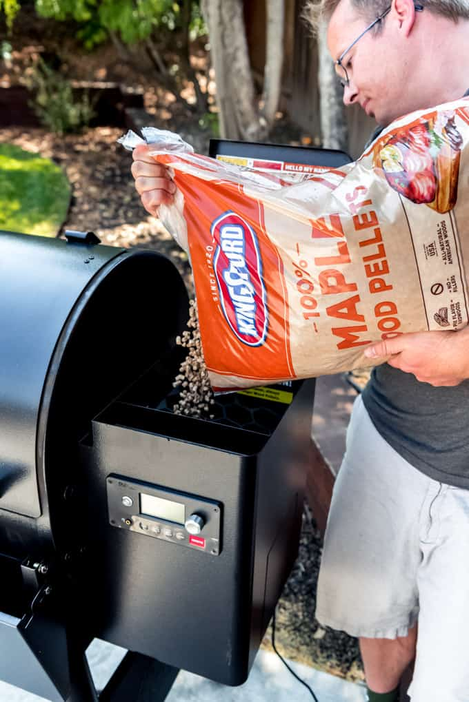 An image of Kingsford 100% Maple Hardwood Pellets being poured into the pellet holder of a Traeger smoker.