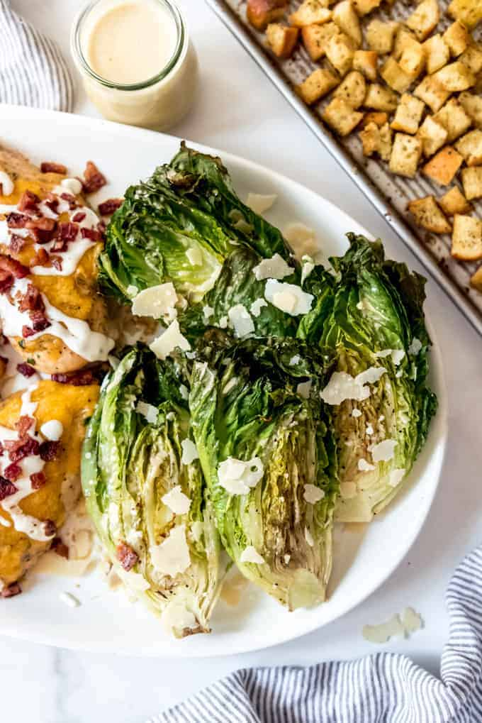 Grilled romaine lettuce drizzled with caesar dressing and sprinkled with Parmesan cheese.
