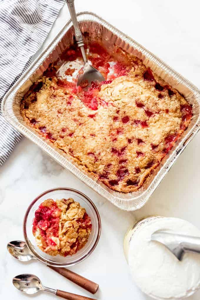 A disposable aluminum pan full of cherry pineapple dump cake with a scoop taken out and placed in a bowl next to it beside a carton of vanilla ice cream.