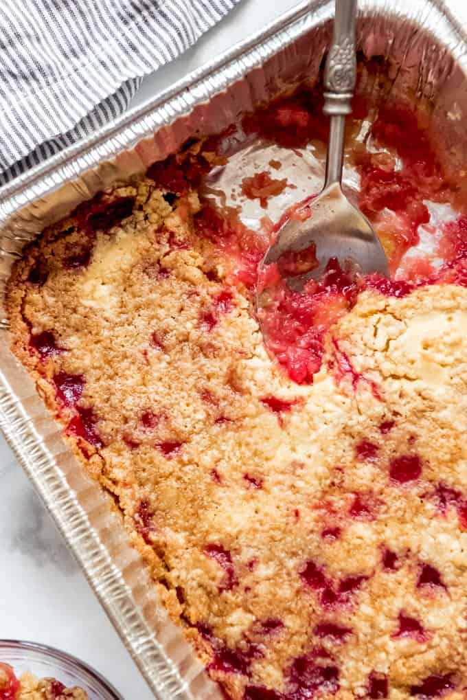 A close image of a serving spoon scooping cherry pineapple dump cake.