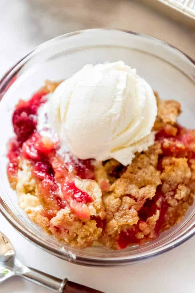 A serving of cherry pineapple dump cake in a glass bowl with a scoop of ice cream.