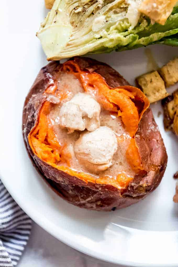 A smoked sweet potato that has been split open and filled with cinnamon honey butter.