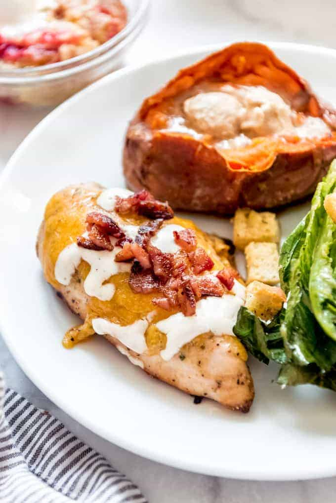 A smoked chicken breast topped with ranch dressing and bacon on a white plate next to a sweet potato and grilled lettuce.