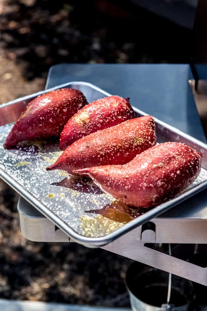 Four sweet potatoes rubbed with olive oil and salt on a baking sheet.