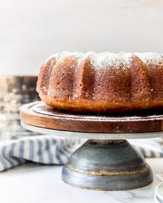 A bundt cake dusted with powdered sugar on a cake stand.