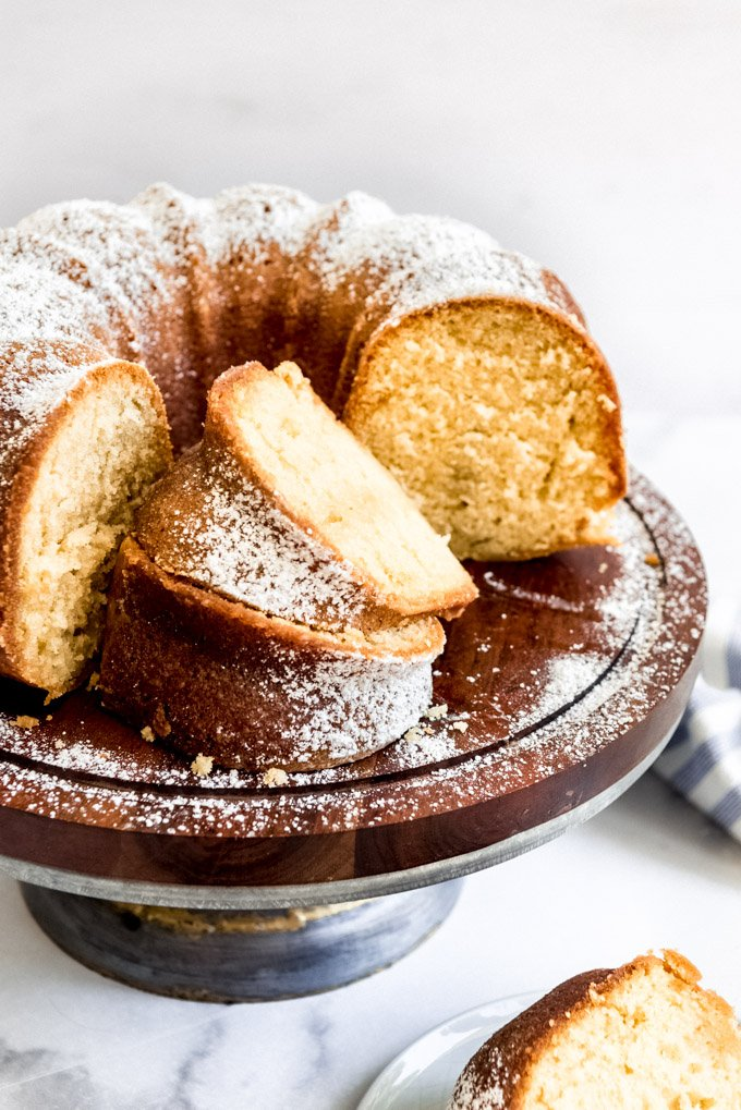 A bundt cake on a wooden cake stand with slices stacked on each other.