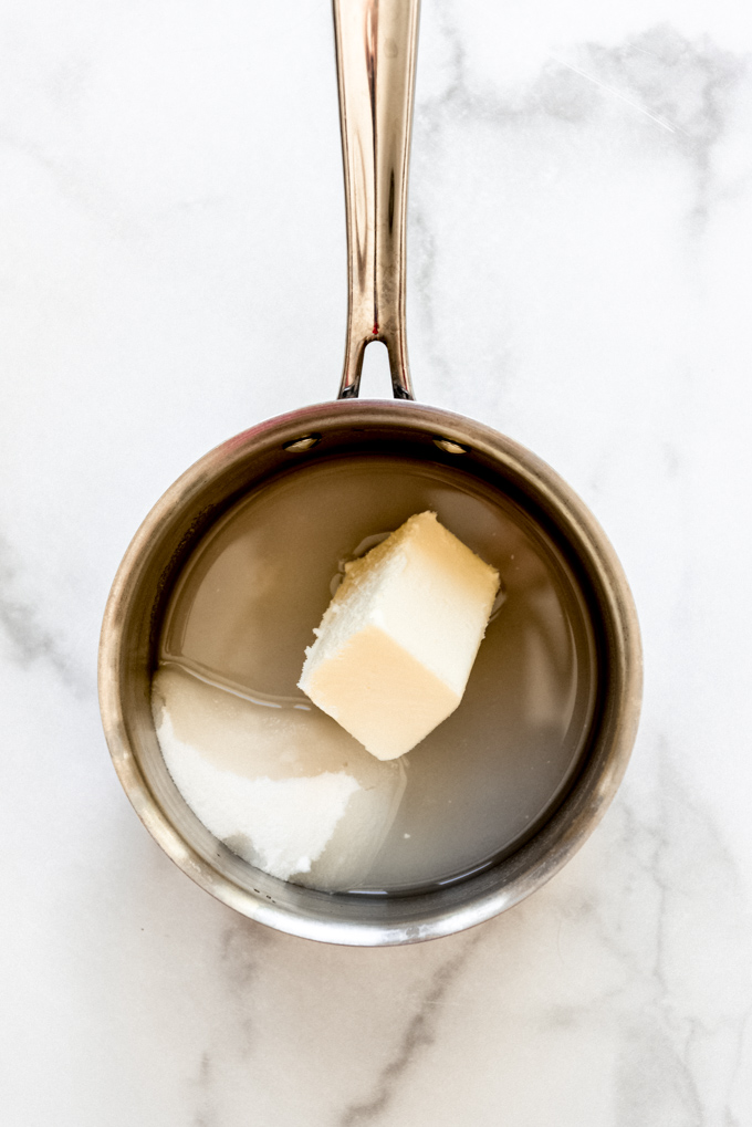 A small saucepan with butter, sugar, and water in it.