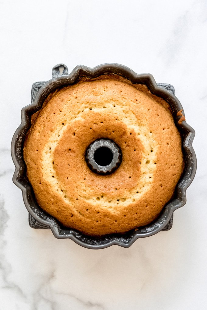 A bundt cake in a pan with holes poked in the top.