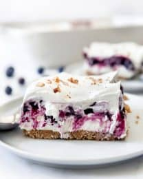 A slice of blueberry delight topped with whipped cream and pecans on a plate.