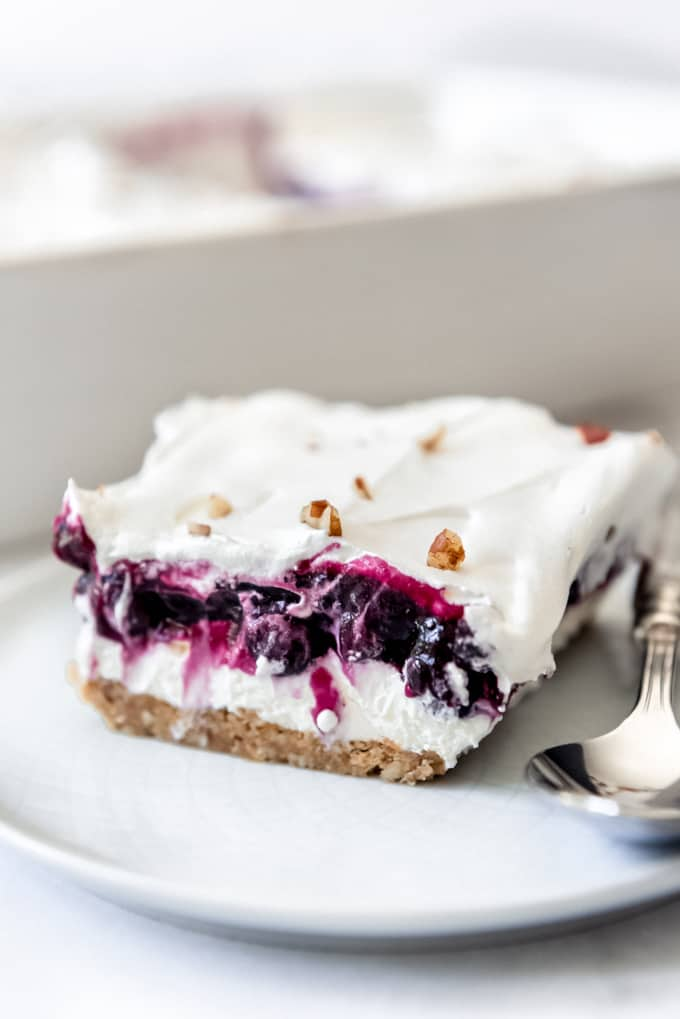 Layers of blueberry filling, whipped cream topping, and creamy filling on a plate.