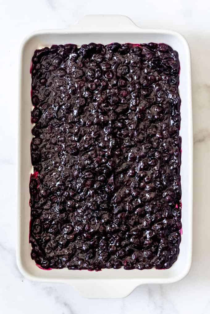blueberry filling spread out in a white baking dish