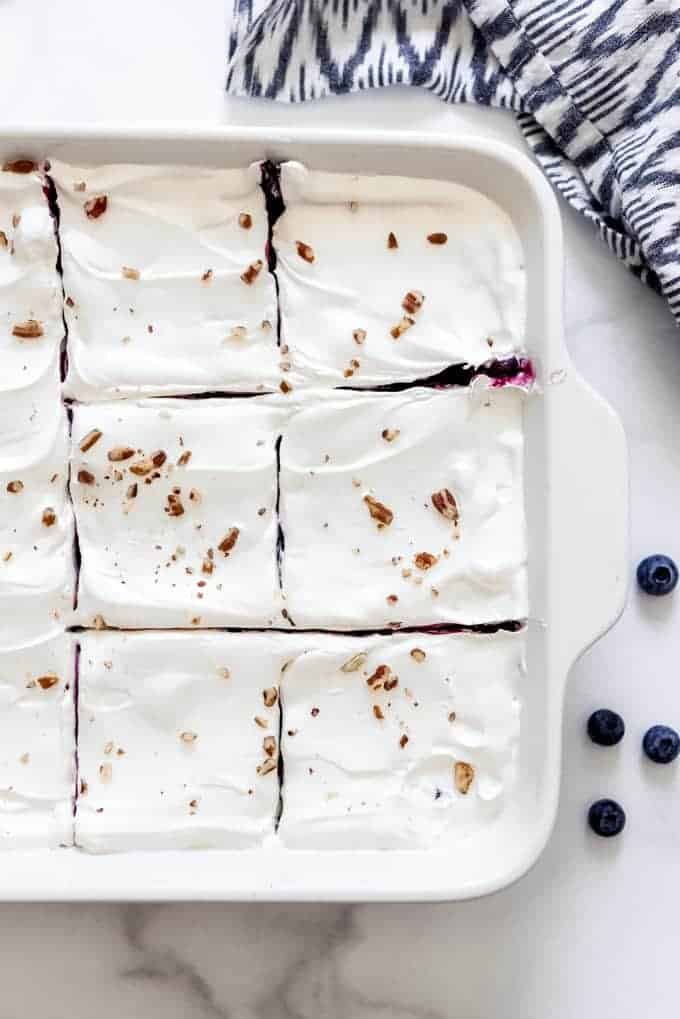 Sliced squares of blueberry delight dessert in a white baking dish.