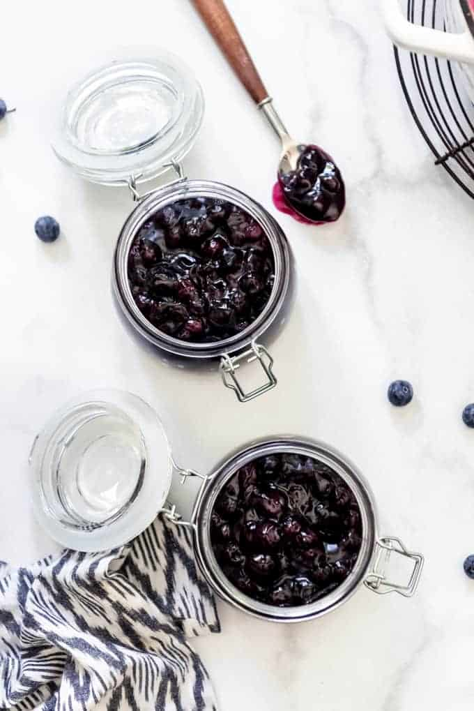 An overhead image of two jars filled with homemade blueberry pie filling.