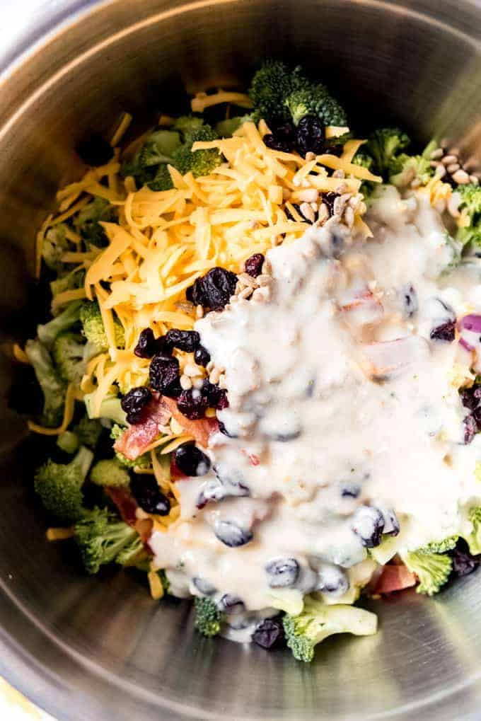 A creamy dressing poured over the components of broccoli salad in a large mixing bowl.