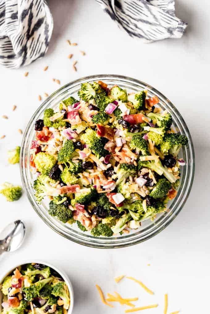 A large serving bowl full of broccoli salad with a smaller individual serving off to the side.
