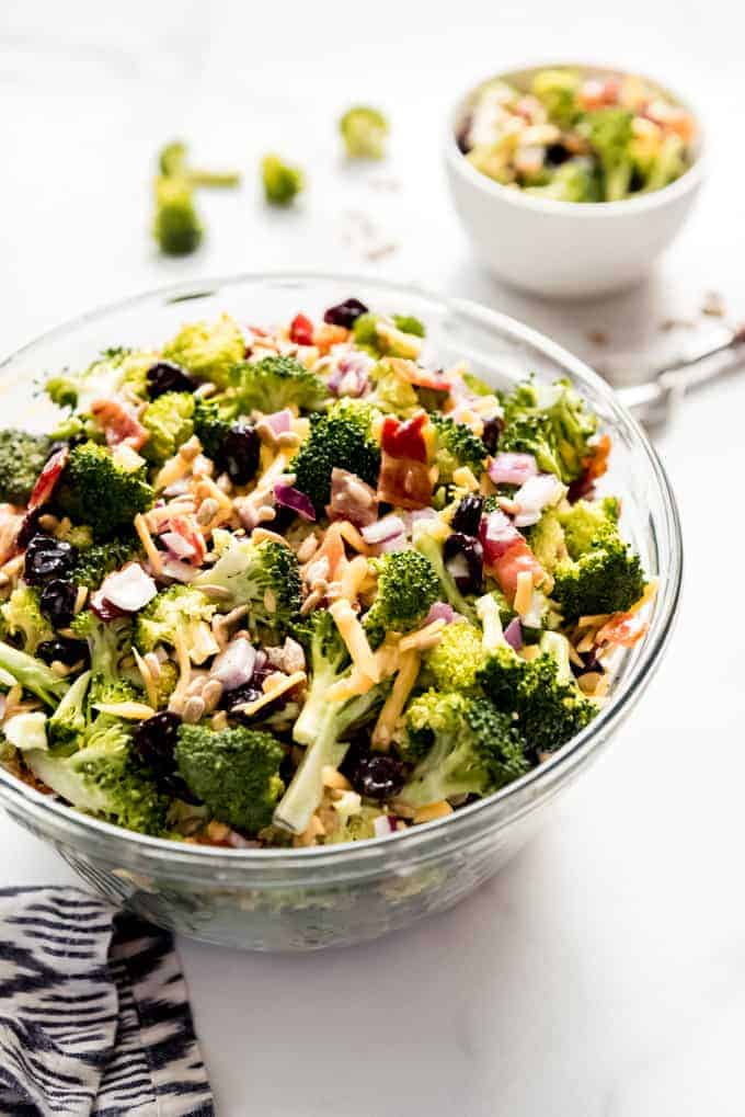 A large glass serving bowl filled with broccoli salad.