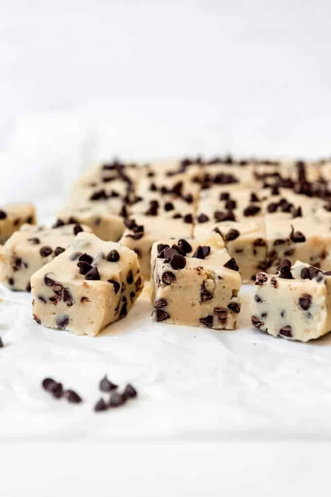 Squares of cookie dough fudge on white parchment paper.