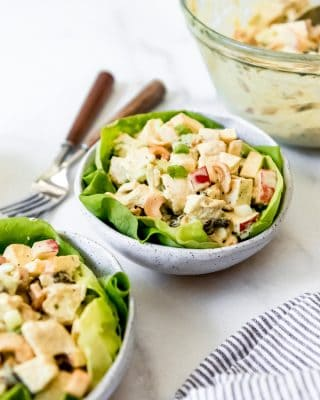 curried chicken salad served in two bowls with a bed of lettuce