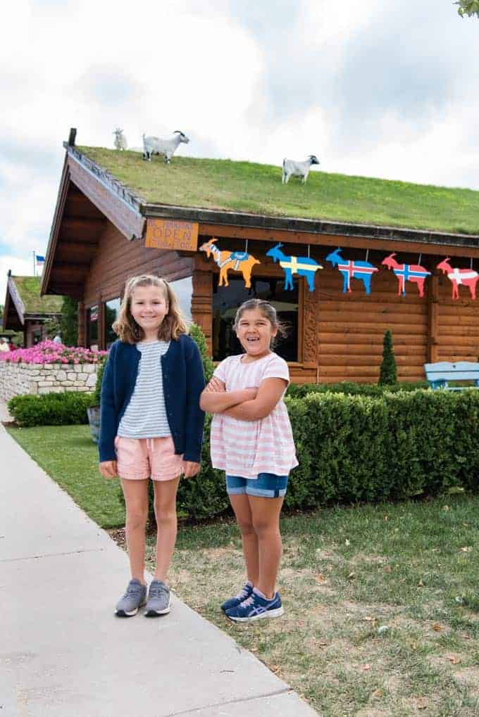 Two children in front of the Al Johnson restaurant with goats grazing on the grass roof.