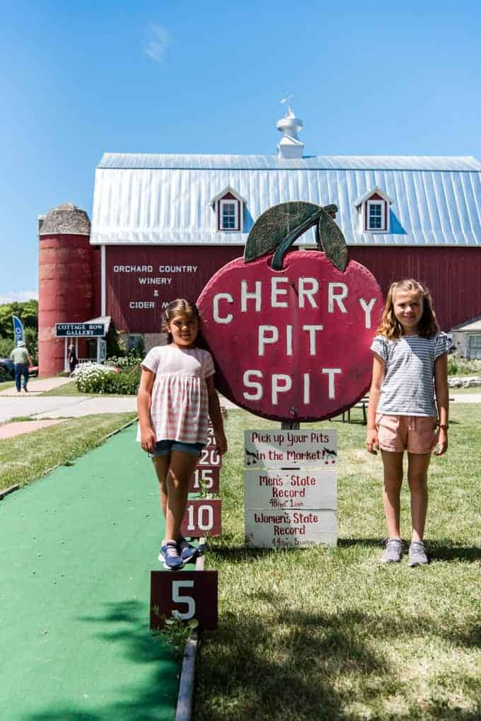 Two children in front of the cherry pit spit sign at Lautenbach's Orchard in Door County, Wisconsin.