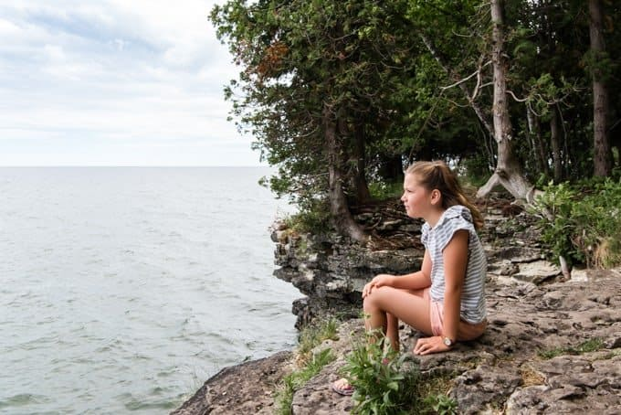 A child looking out over Lake Michigan from Cave Point County Park.