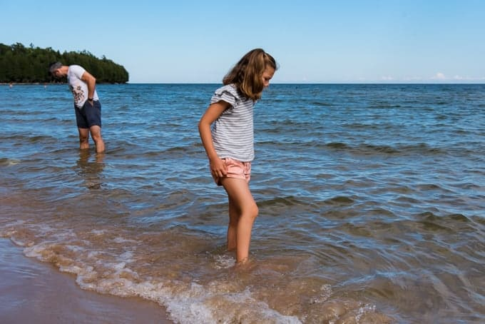A child wading into the waters of Lake Michigan.