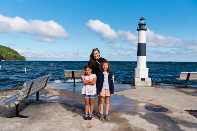 A mother and two daughters in front of a harbor light in Wisconsin.