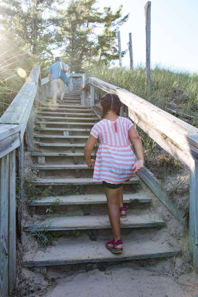 A child hiking up beach stairs at Whitefish Dunes State Park in Door County, Wisconsin.