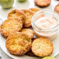 Fried green tomatoes on a white plate with a jar of dipping suace and some whole green tomatoes to the sides