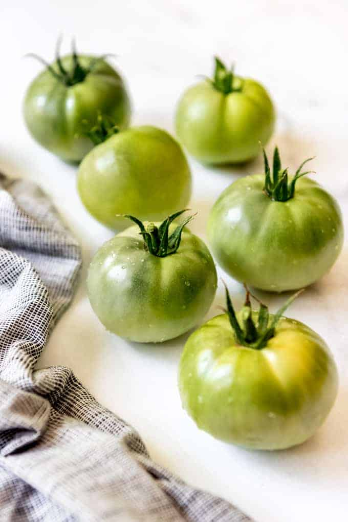 Green tomatoes with water droplets next to a kitchen towel