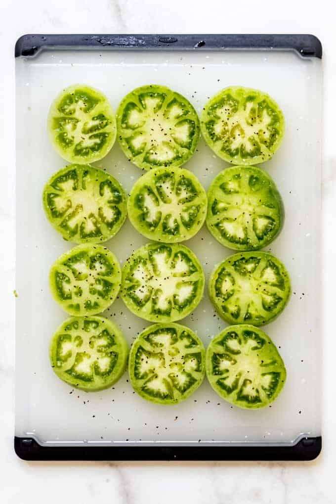 Slices of seasoned green tomatoes on a cutting board
