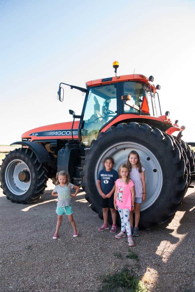 Kids posing in front of large tractor tires.