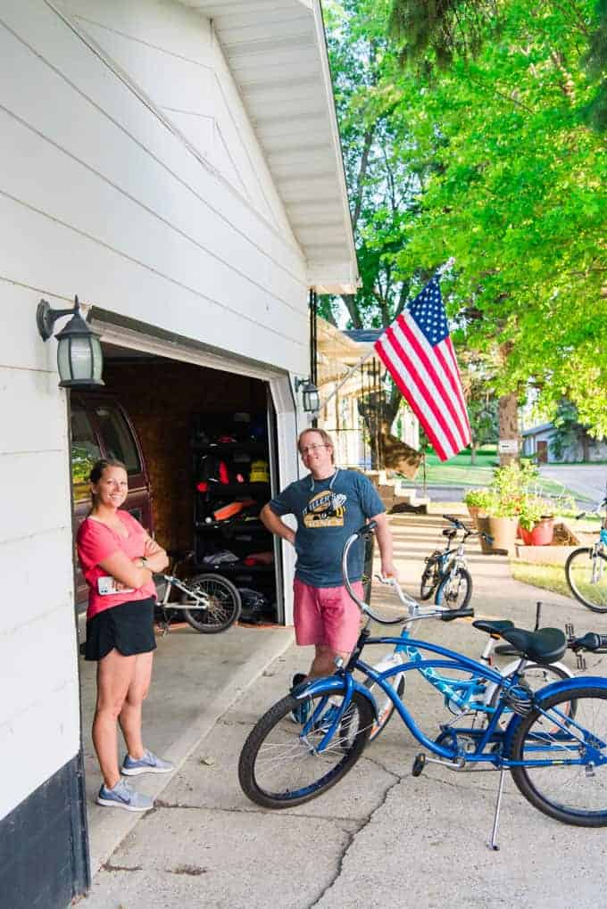 Two people visiting in front of a garage next to bicycles.