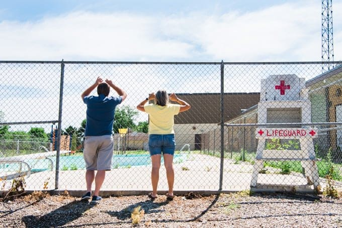 Two people looking through a chainlink fence at an empty swimming pool.