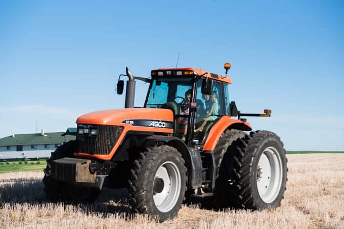 A large orange tractor on a farm.